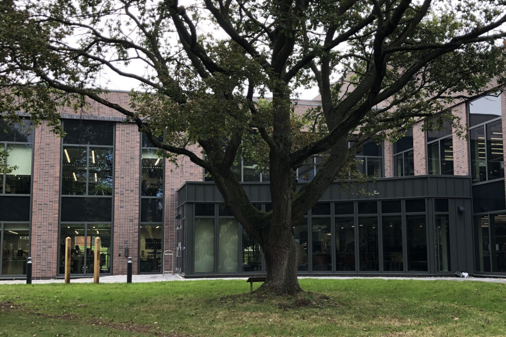 In the foreground is a grassy area and a large oak tree. Behind is a two storey modern building of brick and glass.