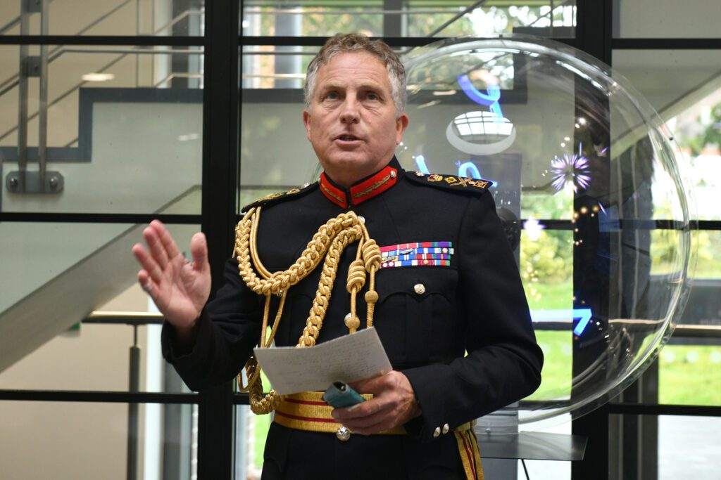 General Sir Nick Carter, a white man wearing a black military uniform with gold braid, stands in front of a glass wall. He is holding a sheet of paper as he makes a speech.