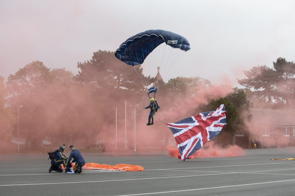 A parachutist from the Silver Stars comes in to land. He has a dark parachute and a union flag flies from him. He is landing on a large concrete open area with buildings behind and there is red smoke in the air.
