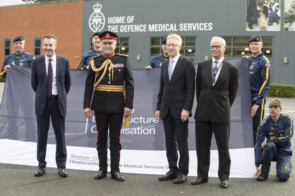 """Three men in suits stand around another man in black military uniform with gold braid and a hat. They stand in front of a large flag with the DIO logo on it, which is being held by a number of men in parachuting suits. Behind them is a large building with text on the side reading """"Home of the Defence Medical Services""""."""