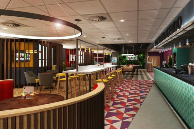 A futuristic looking dining and lounge area. There is a bar, tables and chairs, and a pool table and TV at the far end of the image. The colours across the walls and flooring are bright and varied.