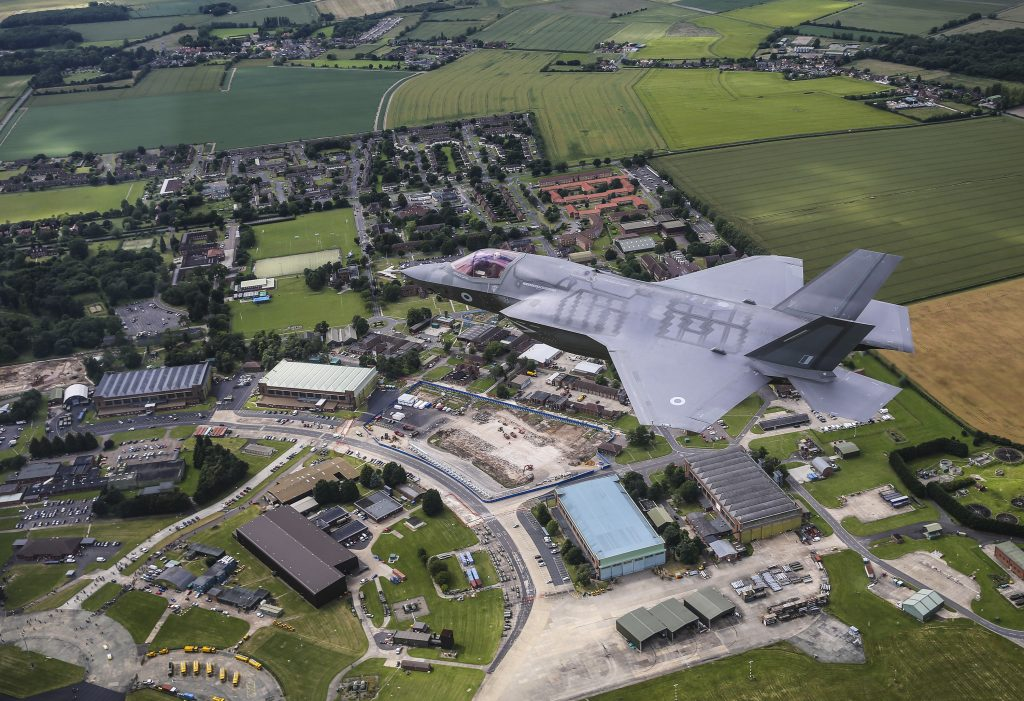 A grey F-35B Lightning aircraft flys over the RAF Marham station. There is a range o hangars and buildings beneath the plane with lots of greenland around the station