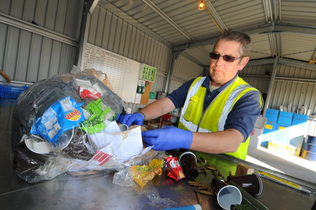 An employee from Landmarc wearing a hi-vis sleeveless jacket with blue gloves and brown glasses is putting away a clear recycling bag . They are some empty coffee cups beside the plastic bag and he is in a grey building with a whiteboard on the left-hand side and blue cabinets behind him.