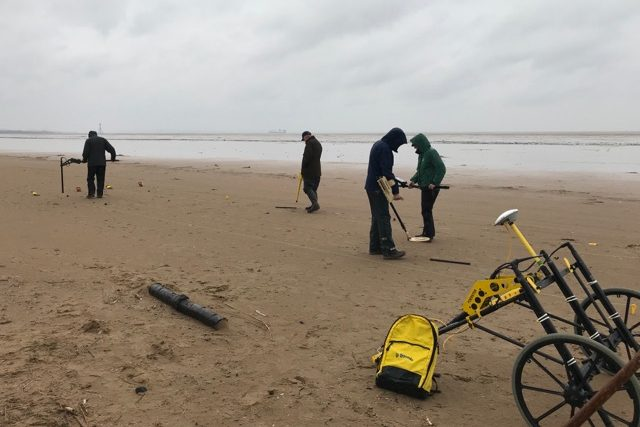 Four people on a beach, using equipment to find buried ordnance. In the foreground is a piece of scanning equipment on a wheel.
