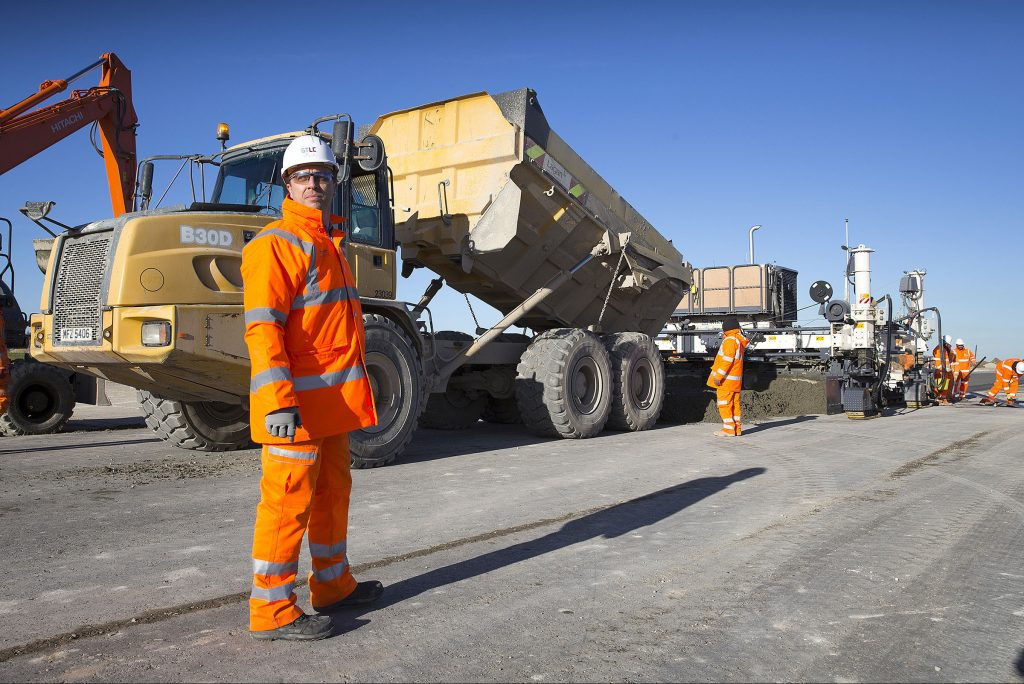A construction worker dressed in orange high-vis and a protective helmet stands on the runway at RAF Marham, with a large vehicle behind.