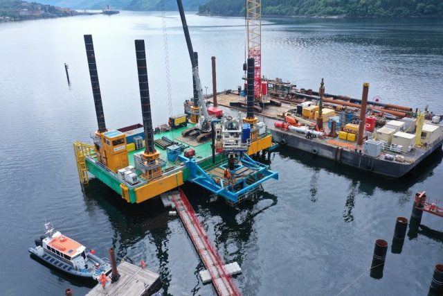 Pictured is the construction site of the Glen Mallan Jetty on the sea. It is square with two black cylinders on it and a construction crane. On the left is a small white boat and pictured behind the jetty are mountains.