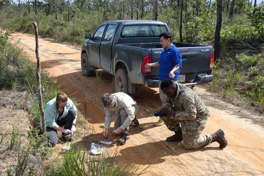 A blue pick up truck is halted on a dirt road. At the rear of it stands a man in a blue polo shirt. In front of him are three people kneeling - a man and a woman in civilian clothing and a man in military uniform. They are working on what appears to be the camera.
