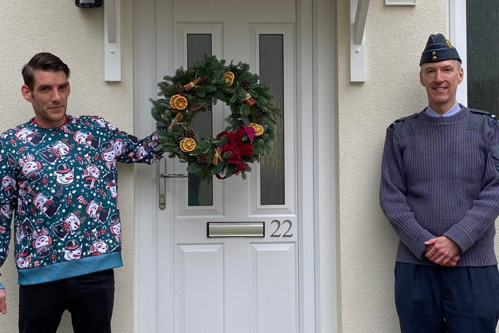 A white man in a Christmas jumper stands to one side of a front door. He holds a Christmas wreath. On the other side of the closed door is another white man in an RAF officer uniform.