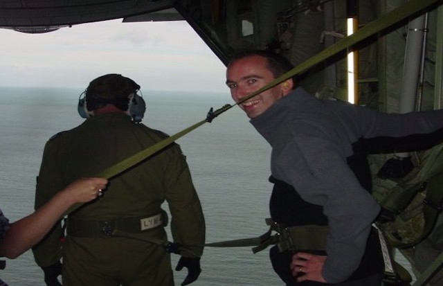Warren is standing in a Hercules C-130J helicopter. Behind him the door is open, with an individual in headphones standing by him and the view of the sea.