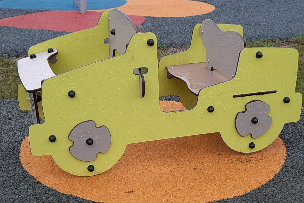 A car toy which children can sit inside on a playground. The car sits on an orange circle on the surface of the play park.
