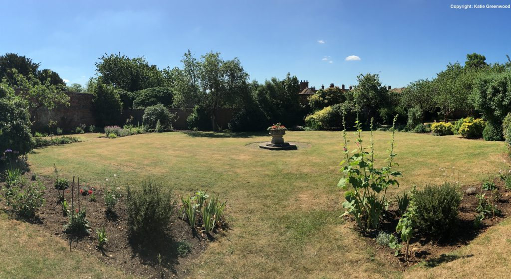 Pictured of a large open garden with newly restored flower beds. A small round monument is in the middle with flowers on it and flowerbeds are located on left and right side of the garden. There are trees at the back of the garden and it is a sunny day.